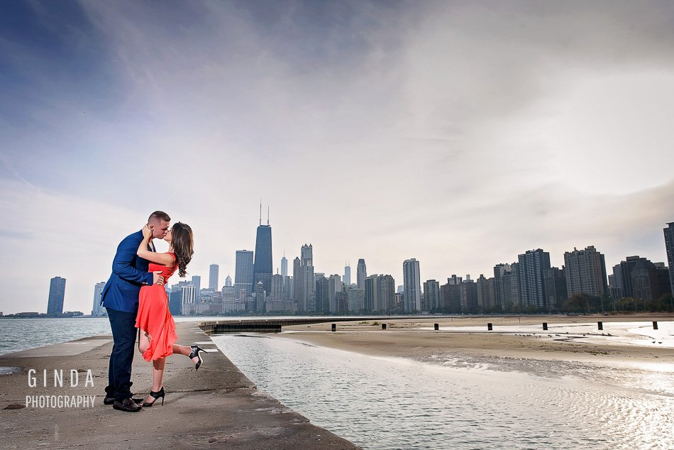 engaged couple kissing in front of the city of chicago