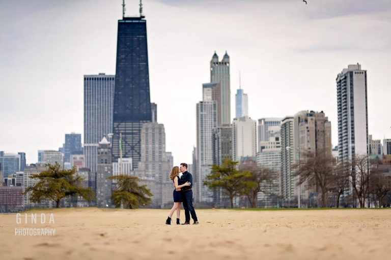 chicago skyline engagement with couple kissing on sand