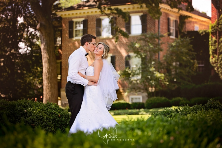 beautiful couple kissing during wedding in cantigny park