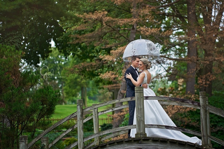 couple cuddling on a wooden bridge during chicago rainy day wedding